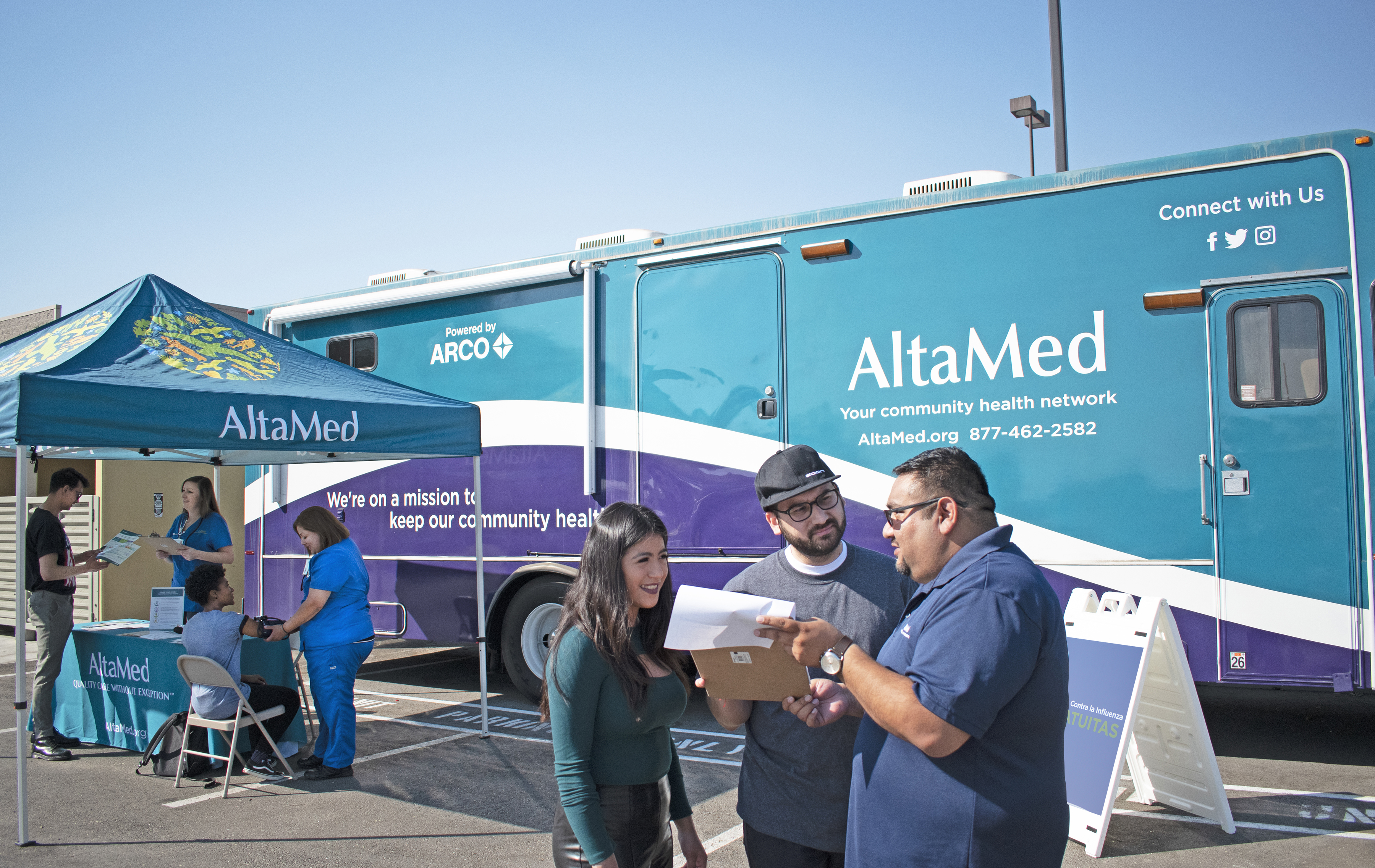 People standing in front of AlatMed mobile clinic